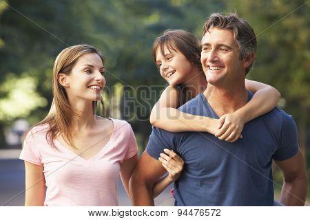 Dad Giving Daughter Piggyback On Family Walk Through Summer Park