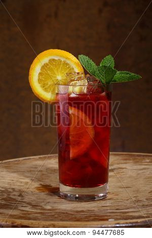 Wine Of Sangrija In A Transparent Glass With An Orange, Mint And Ice Cubes On A Wooden Table