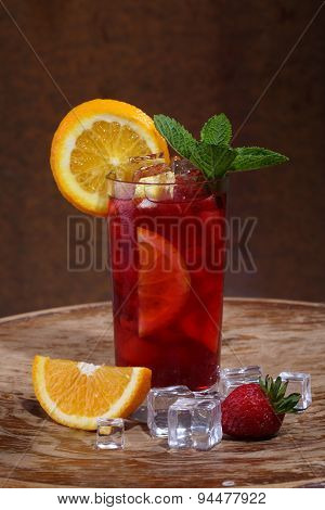 Wine Of Sangrija In A Transparent Glass With A Strawberry, An Orange And Mint On A Wooden Table