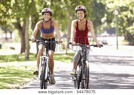 Two Women Cycling Through Park