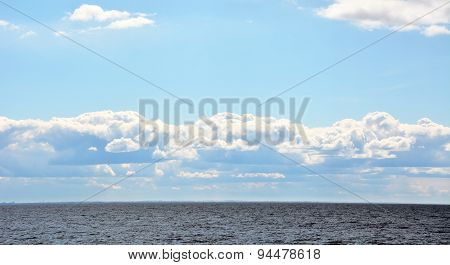 Puffy Clouds Over The Sea At Sunny Day