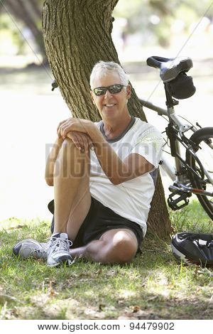 Mature Man Resting On Cycle Ride Through Park