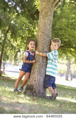 Two Children Hugging Tree In Park