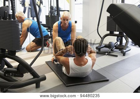 Man Working With Personal Trainer In Gym
