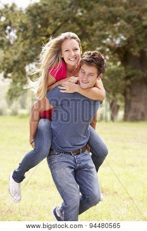 Young Man Giving Woman Piggyback On Walk Through Countryside