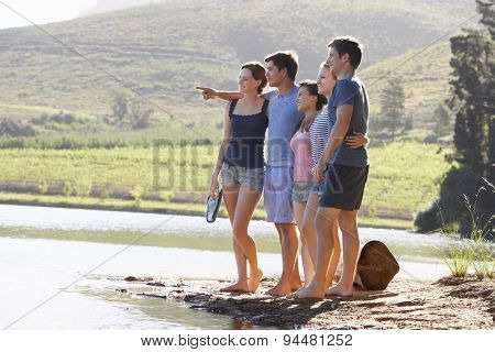 Group Of Young People Standing At Shore Of Lake Splashing Water