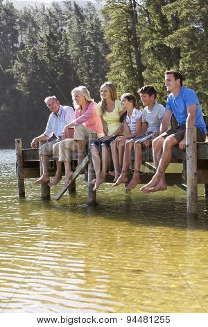 Three Generation Family Sitting On Wooden Jetty Looking Out Over Lake