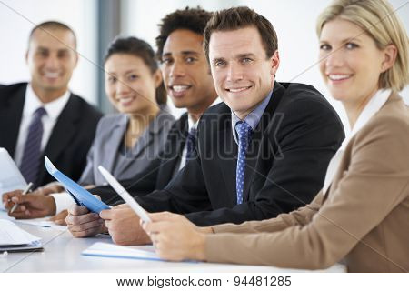 Portrait Of Male Executive Attending Office Meeting With Colleagues