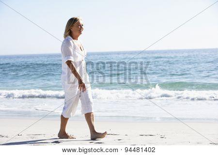 Senior Woman Walking along Sandy Beach
