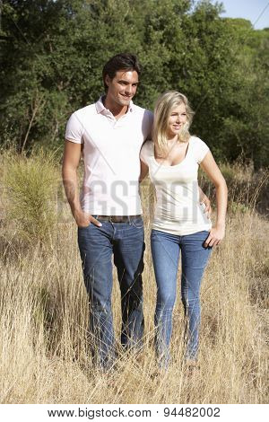 Young Couple Walking Through Summer Countryside