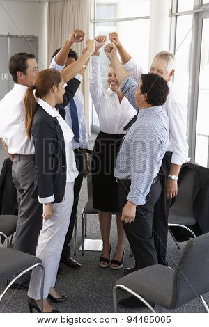 Group Of Businesspeople With Arms Raised At Company Seminar
