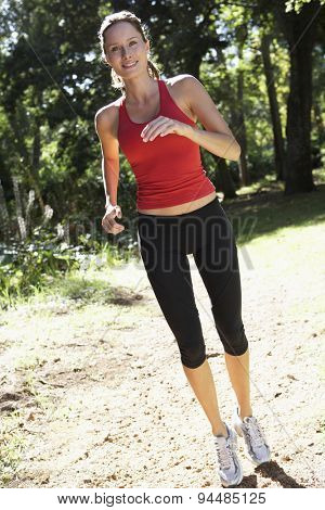 Young Woman Jogging Through Woods