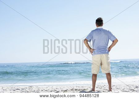 Senior Man On Holiday Standing On Sandy Beach