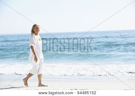 Woman Walking along Sandy Beach