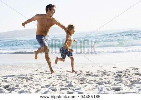 Father And Son Running Along Beach Together Wearing Swimming Costumes