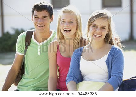 Group Of Teenage Students Sitting On Bench