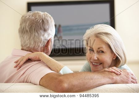 Senior Couple Watching Widescreen TV At Home