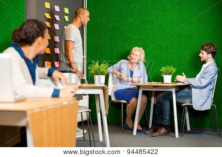 A creative session, with a small project team, with various colored sticky notes on a wall, containing ideas and solution. A woman looks over her shoulder at teamwork taking place behind her.