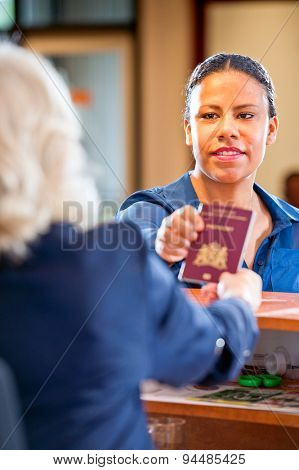 Receptionist hands over a passport to a tourist at te front desk and reception of a hostel