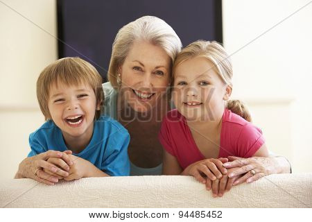 Grandmother And Grandchildren Watching Widescreen TV At Home