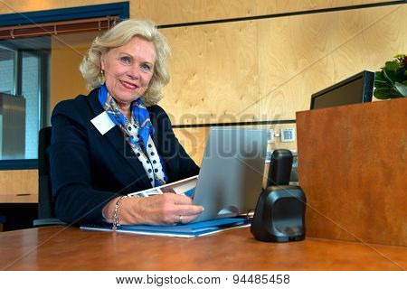 Smiling senior receptionist sitting at the front desk as an example of successful reintegration after retirement.