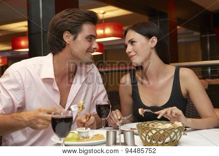 Young Couple Enjoying Meal In Restaurant