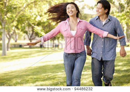 Asian couple running through in park