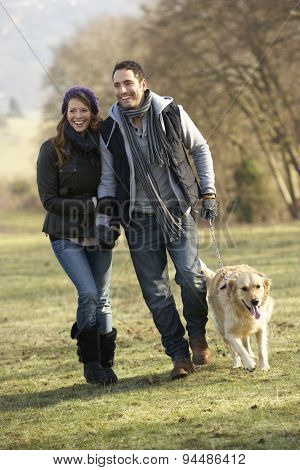 Couple walking golden retriever in the country