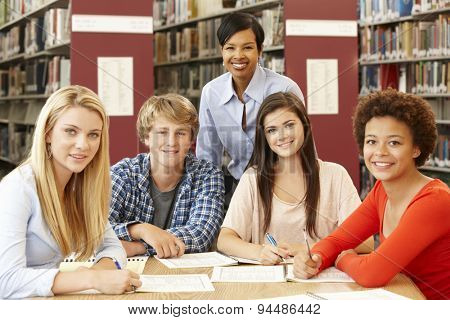Group of students working in library with teacher