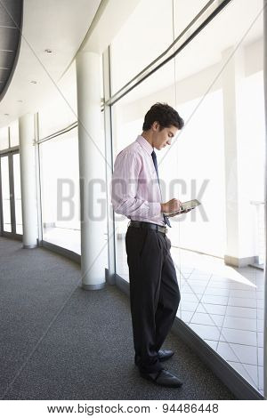 Young Businessman Standing In Corridor Of Modern Office Building Using Tablet Computer