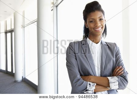 Young Businesswoman Standing In Corridor Of Modern Office Building
