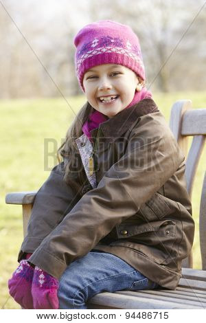 Portrait young girl sitting outdoors in winter