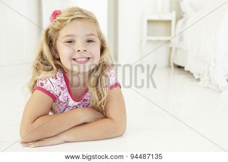 Young Girl Relaxing On Floor In Bedroom