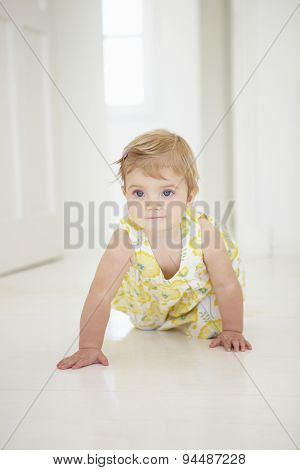 Young Girl Crawling On Floor In Bedroom