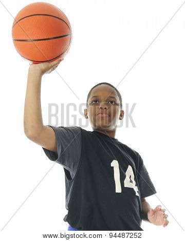 Half-length low angle image of a preteen boy attempting to make a one handed basketball shot.  On a white background.