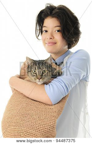 A young teen girl happily holding her pet Tabby cat in a tan, woven shoulder bag.  On a white background.