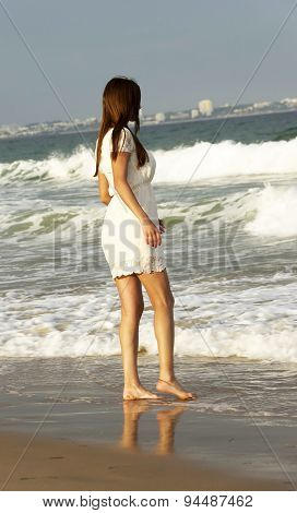 Young brunette girl enjoying the sunset on the beach