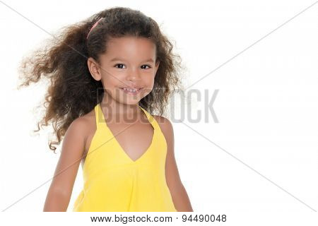 Cute small hispanic girl wearing a yellow summer dress isolated on white