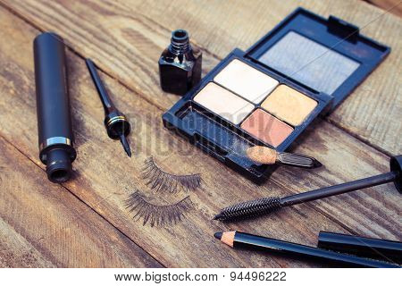 Cosmetics for eyes: pencil, mascara, eyeliner, false eyelashes and eye shadow. Toned image.