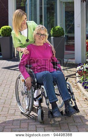 Nurse With Senior Woman In Wheelchair Outdoors