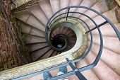 foto of staircases  - High Angle View of Spiral Staircase Winding Downward in Historical Building - JPG