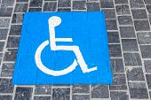 stock photo of handicapped  - An handicap symbol painted on the stone road - JPG