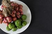 picture of red shallot  - Raw bergamot and shallot in a plate on black background - JPG