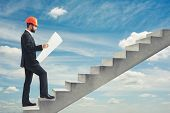 picture of follow-up  - businessman in orange hardhat holding blueprint and following up on concrete stairs over blue sky - JPG