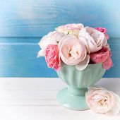 pic of blue rose  - Pastel roses in turquoise vase on white wooden background against blue wall - JPG