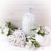 picture of caged  - Background with tender apple blossom decorative heart and candle in decorative bird cage on white painted wooden planls - JPG