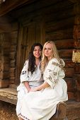 foto of national costume  - Two ukrainian girls in national costumes at the old wooden house porch - JPG