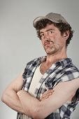 stock photo of hillbilly  - Confident redneck folds his dirty arms while smoking a cigarette - JPG