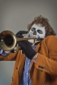 pic of clown face  - Professional trumpet player with face painted as human skull - JPG