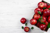 pic of wooden crate  - Ripe red apples in crate on wooden background - JPG